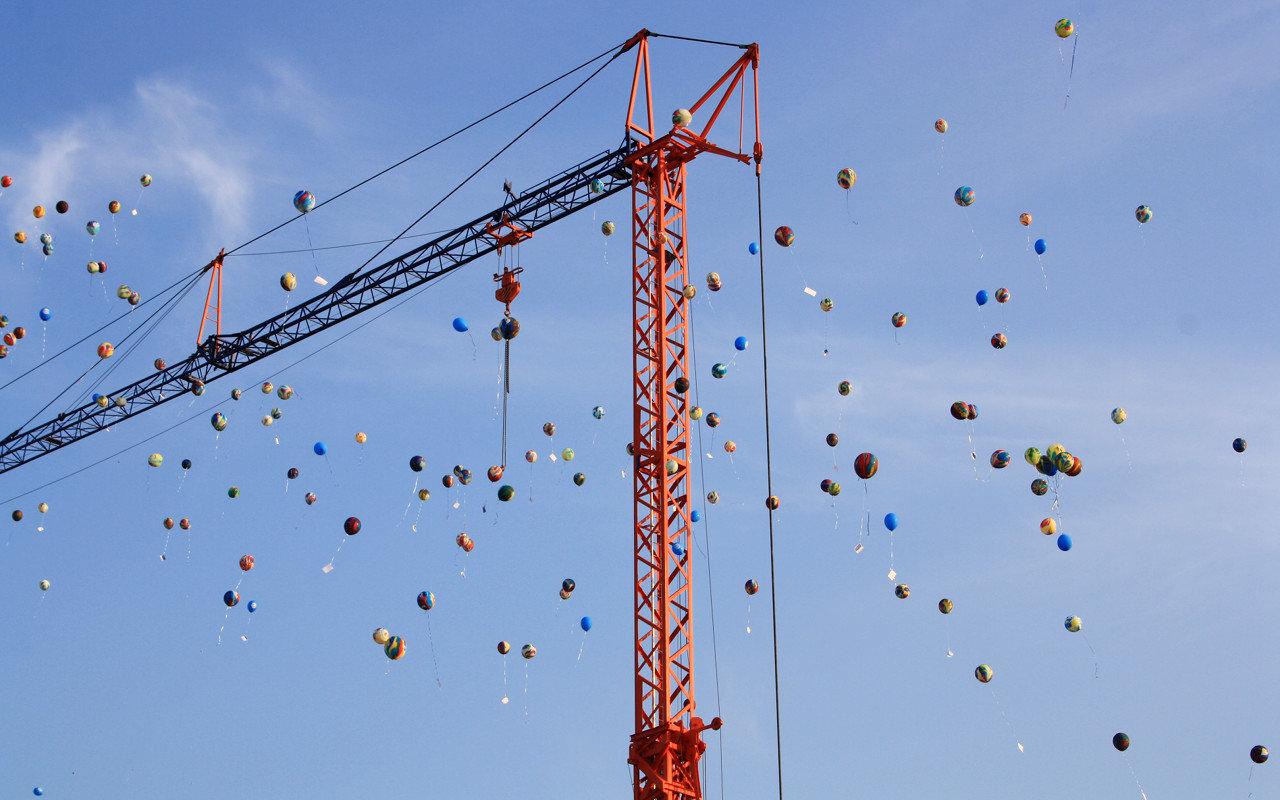 300 Luftballons vom Barne-Kindersommerfest fliegen an einem Baukran vorbei, bevor sie ihre weitere Reise antreten | Foto: Daniel Schneider