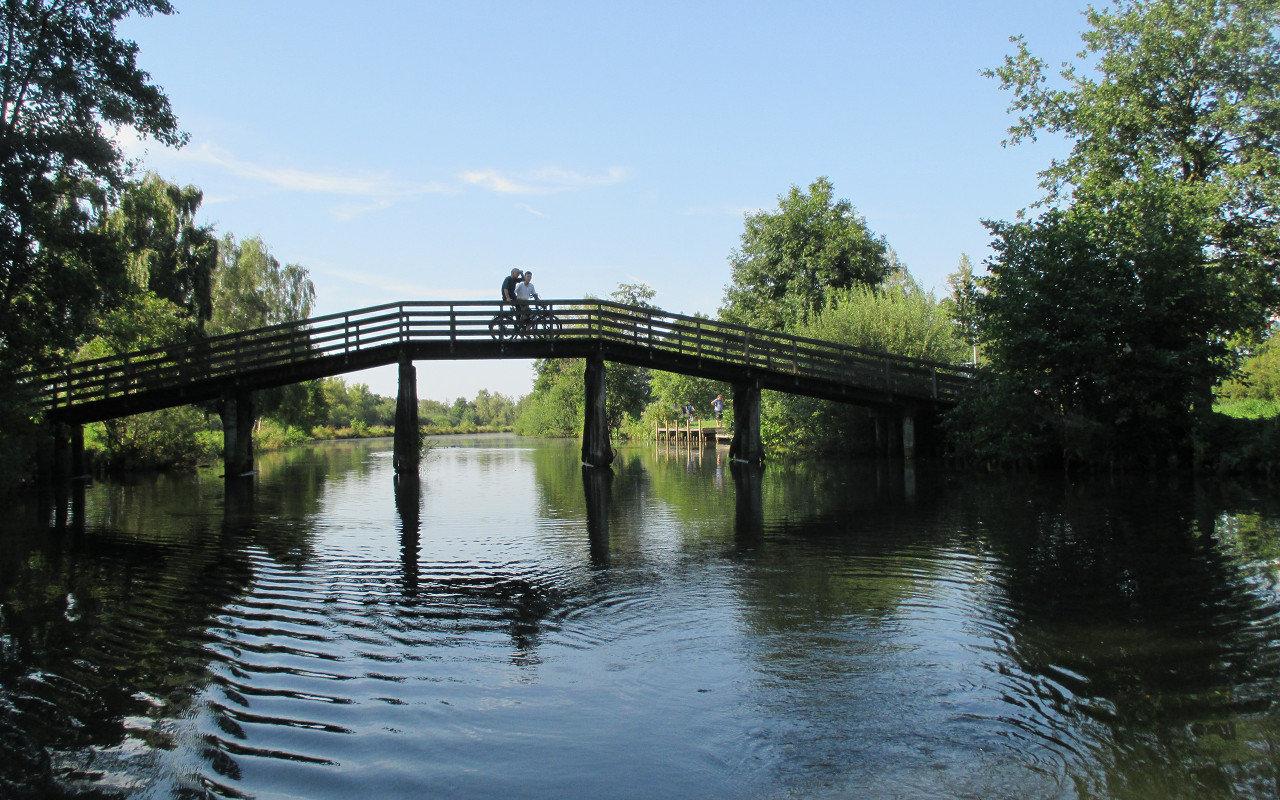 Zwei Radfahrer legen auf der Holzbrücke über den Hagenburger Kanal eine kurze Rast ein. Die Brücke verbindet Sachsenhagen und Wunstorf. Wer sie unterquert und dem Wasserlauf folgt, gelangt ins Steinhuder Meer. | Foto: Daniel Schneider