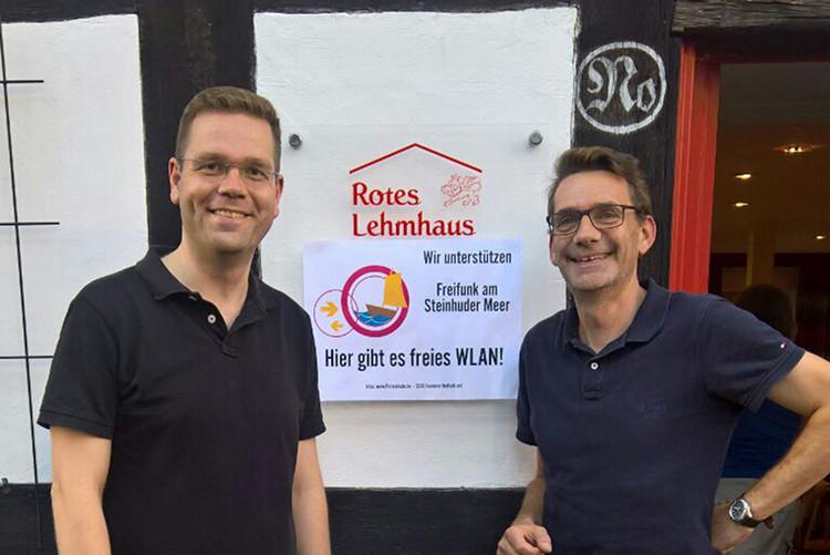 Torben Klant und Bernd Maschke präsentieren das Freifunk-Hinweisschild am Roten Lehmhaus | Foto: Privat