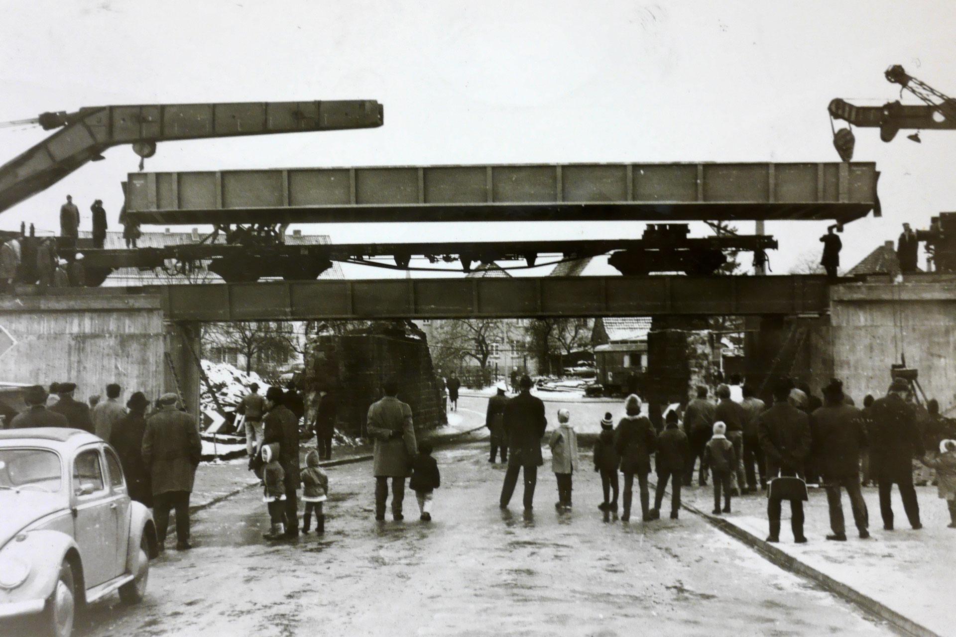 Am 03. Dezember 1969 schauten Wunstorfer Passanten neugierig zu, wie an der Kolenfelder Straße Eisenbahnträger für die neue Eisenbahnbrücke geliefert wurden. | Foto: Stadtarchiv Wunstorf, Nachlass Armin Mandel