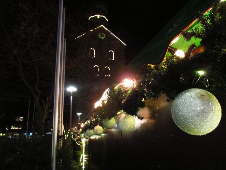 Christbaumkugeln an einer Bude, im Hintergrund die beleuchteten Umrisse der Wunstorfer Stadtkirche | Foto: Daniel Schneider