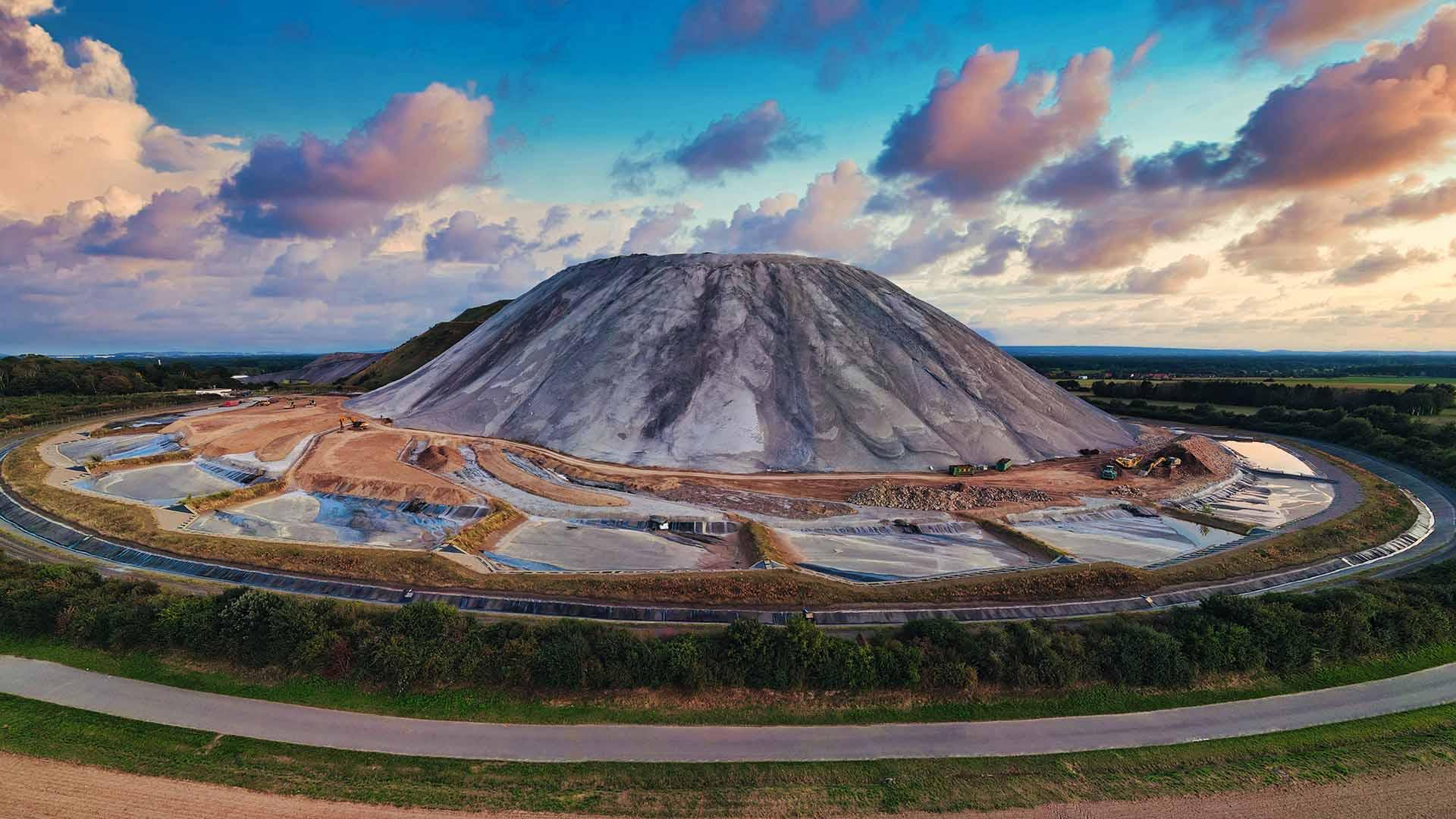 """Auf ca. 140 Metern Höhe ist der """"Kalimandscharo"""" seit dem ersten Salzabbau im Jahr 1898 angewachsen. Am 21. Dezember 2018 wurde der Bergbau von K+S wegen Unwirtschaftftlichkeit eingestellt. Die Grube Sigmundshall war mit knapp 1.475 Metern inzwischen das tiefste Kalibergwerk weltweit."""